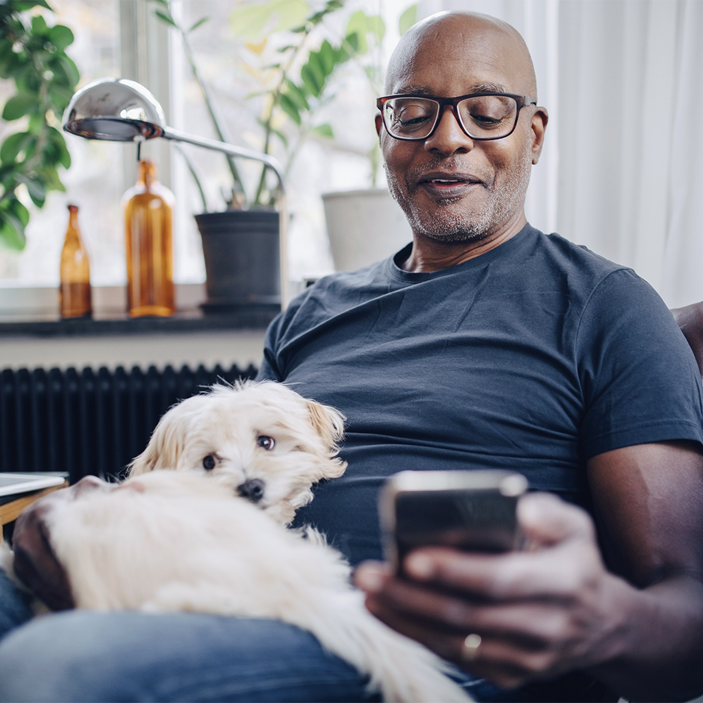 A man with a small dog in his lap looks at his smart phone.