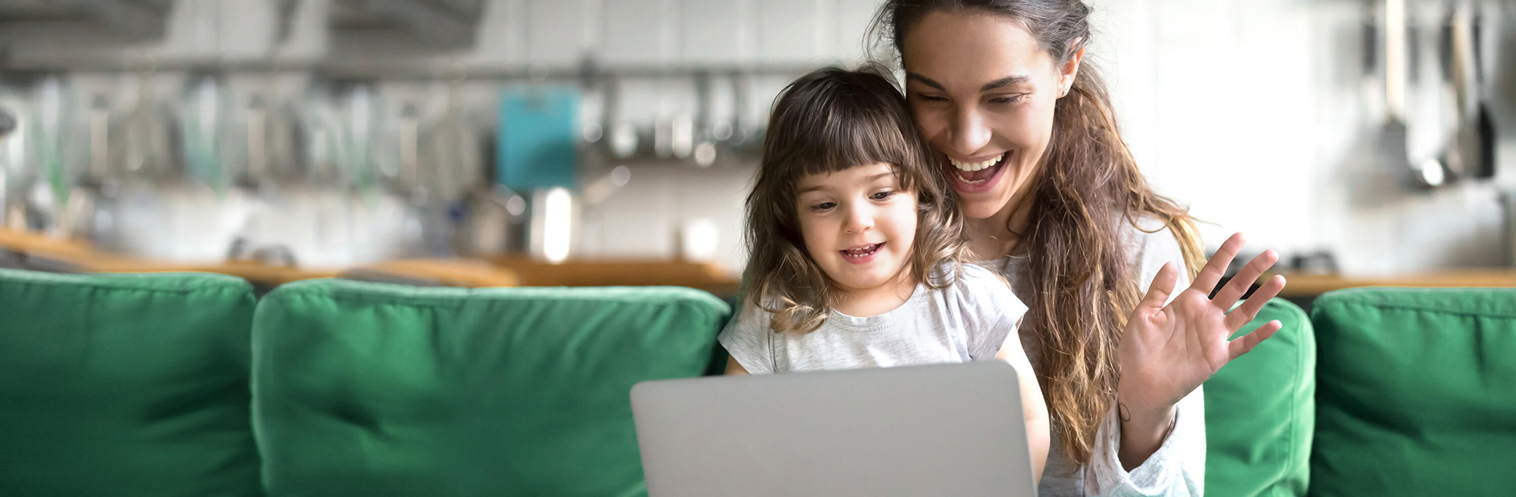 A mother and her young daughter smile as they look at a laptop screen.