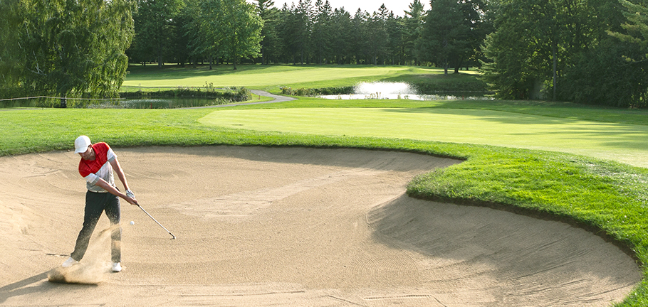 A golfer takes a shot from the bunker.