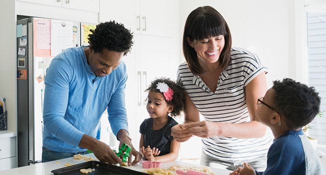 A man and a woman play with two young children inside their kitchen.