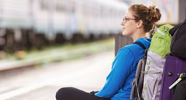 A female backpacker waits on a train platform.