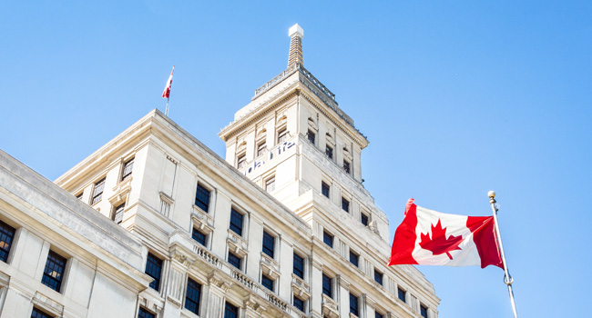 The facade of the Canada Life building in Toronto with the Canada flag in the foreground.