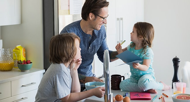 A man and two young kids laugh together in a kitchen.