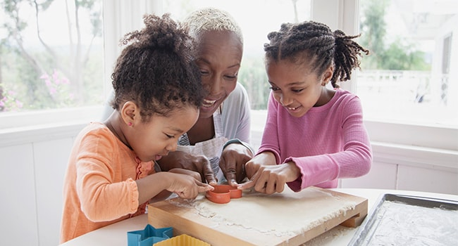 A woman and two young children have fun with play-dough.